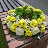 Kompozycja z kwiatów żywych; wielkość: średnica ok. 40 cm; margarytka żółta żółta, róża kremowa (Avalanche), zieleń dekoracyjna.