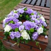 Kompozycja z kwiatów żywych; wielkość: średnica ok. 40 cm; eustoma fioletowa, róża kremowa (Avalanche), margarytka zielona (Santini), zieleń dekoracyjna.