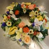 Kompozycja z kwiatów sztucznych; wielkość: średnica ok. 40 cm; kwiaty i dodatki sztuczne utrzymane w tonacji kremu, beżu i pomarańczy z dodatkiem fioletu.