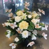 Kompozycja z kwiatów sztucznych w plastikowej misie; wielkość: ok. 50 cm; kwiaty i dodatki sztuczne utrzymane w tonacji bieli, kremu i różu; misa obciążona gipsem, nie pozostawia śladów na pomniku.