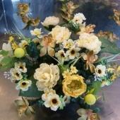Kompozycja z kwiatów sztucznych w plastikowej misie; wielkość: ok. 50 cm; kwiaty i dodatki sztuczne utrzymane w tonacji żółci, zieleni i kremu; misa obciążona gipsem, nie pozostawia śladów na pomniku.