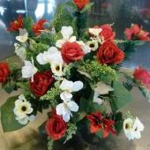 Kompozycja z kwiatów sztucznych w plastikowej misie; wielkość: ok. 50 cm; kwiaty i dodatki sztuczne utrzymane w tonacji czerwienie, zieleni i kremu; misa obciążona gipsem, nie pozostawia śladów na pomniku.