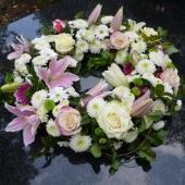 Kompozycja z kwiatów żywych w gąbce florystycznej; wielkość: średnica ok. 50 cm; lilie różowe i białe, róża kremowa (Avalanche), margarytka (Ibis, Bacardi, Santini), zieleń dekoracyjna.