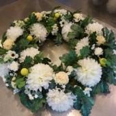 Kompozycja sezonowa z kwiatów sztucznych w formie okręgu; wielkość: średnica ok. 90 cm; chryzantemy kremowe, sztuczne kwiaty i dodatki utrzymane w jasnej tonacji.
