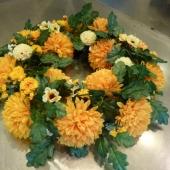 Kompozycja sezonowa z kwiatów sztucznych w formie okręgu; wielkość: średnica ok. 70 cm; chryzantemy żółte, sztuczne kwiaty i dodatki utrzymane w kremowej tonacji.