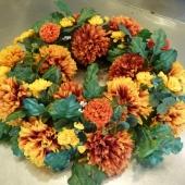Kompozycja sezonowa z kwiatów sztucznych w formie okręgu; wielkość: średnica ok. 70 cm; chryzantemy brązowe, sztuczne kwiaty i dodatki utrzymane w żółtej tonacji.