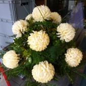 Kompozycja sezonowa z kwiatów sztucznych na żywym podkładzie w gąbce florystycznej; wielkość: duża; 12 kremowych chryzantem, podkład jodłowy, zieleń dekoracyjna
